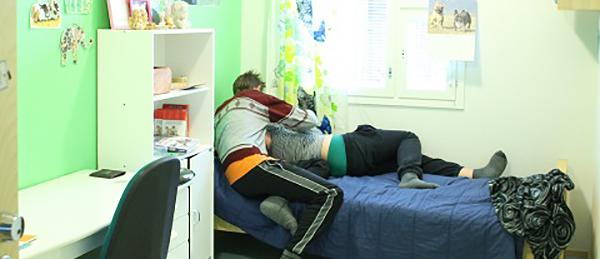 Kuvassa on nuoren ihmisen huone. Nuori makaa sängyllä ja toinen henkilö nojaa nuoreen.