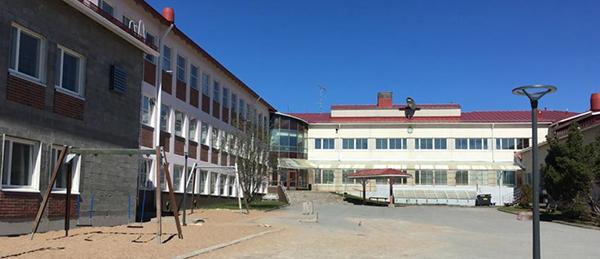 Kuvassa on valkoinen rakennus, jonka pihassa on keinuja ja pyöräteline.