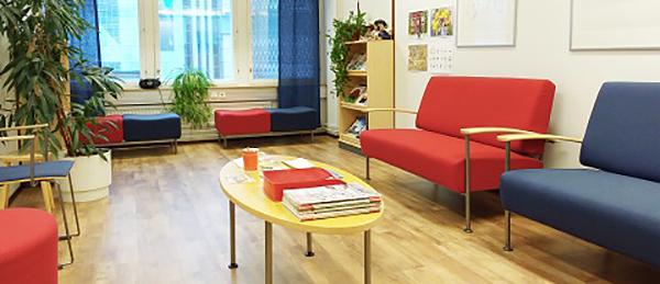 Kuvassa on odotustila, jossa on tuolia, pöytä ja kasvia.