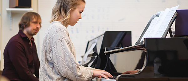 Kuvassa on henkilö soittamassa pianoa. Toinen henkilö itstuu taaempana.