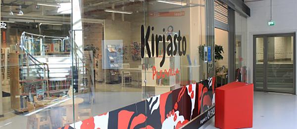 Kuvassa on kauppakeskuksen käytävä ja kirjaston lasi-ikkuna.