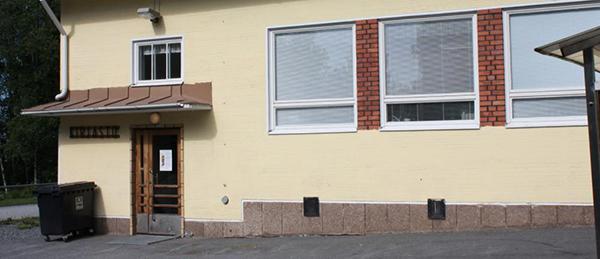 """Kuvassa on vaalea rakenus ja ovi. Oven vieressä on kyltti, jossa lukee """"kirjasto""""."""