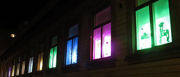 Kuvassa on ikkunoita, joista heijastuu eri värisiä valoja.