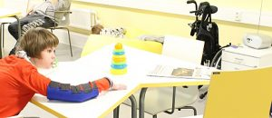 Kuvassa on lapsi leikkimässä pöydän äärellä.