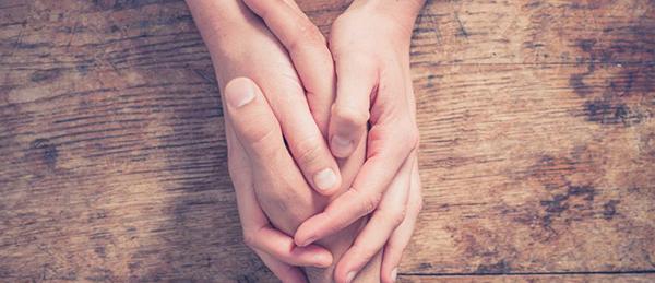 Kuvassa on yhden henkilön kädet, jotka pitävät kiinni toisen henkilön kädestä.
