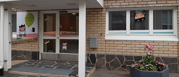 Kuvassa on Lasten kulttuurikeskus Kruunupään pääovi. Ikkunoissa näkyy Kruunupään piirretty maskottiukko.