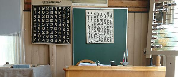 Kuavssa on vanha luokkahuone, jossa on pulpetti, opettajanpöytä, liitutaulu ja helmitaulu.