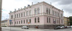 Kuvassa on vaaleanpunainen rakennus ja katua.