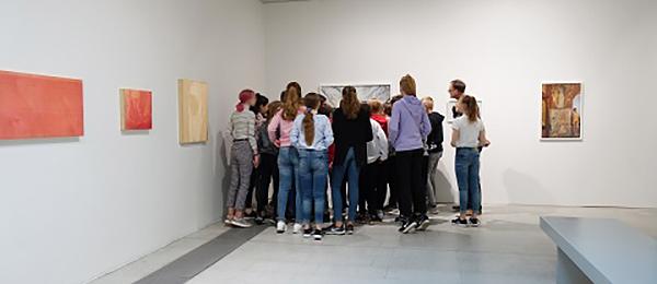 Kuvassa on taidegallerian huone, jonka nurkkaan on kokoontunut nuoria katselemaan taideteosta.