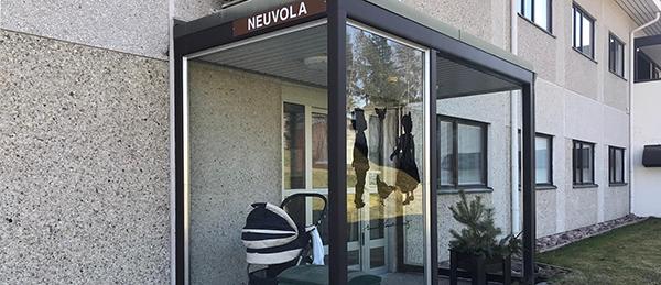 """Kuvassa on pääovi ja lasitettu katos, jossa lukee """"Neuvola""""."""