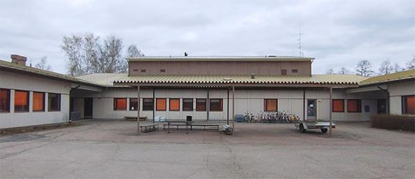 Kuvassa on vaalea matala rakennus sekä iso etupiha.