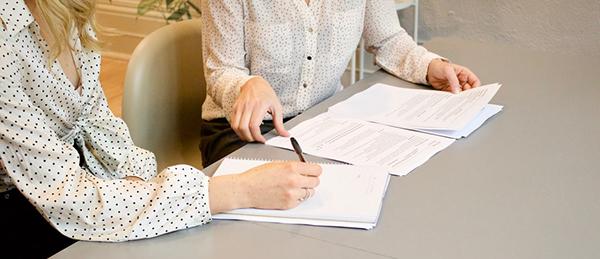 Kuvassa on kaksi henkilöä lukemassa papereita.