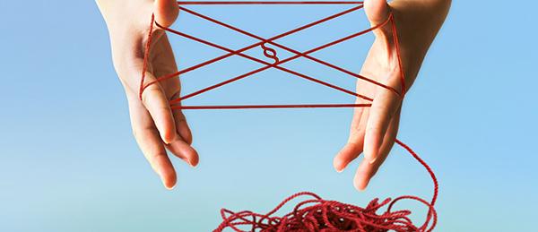 Kuvassa on kaksi kättä, jotka selvittävät lankakerää.
