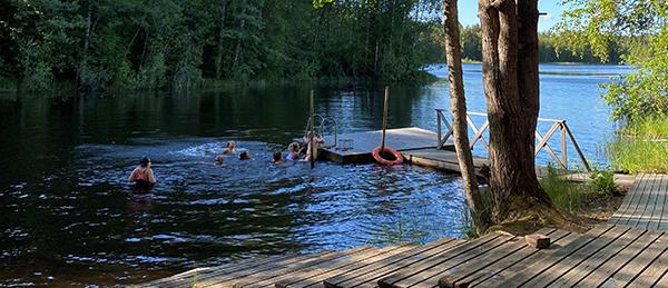 Kuvassa on ihmisiä uimassa ja laituri.