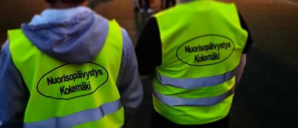 Kuvassa on kaksi turvaliiviin pukeutunutta henkilöä selkä kuvaajaan päin.