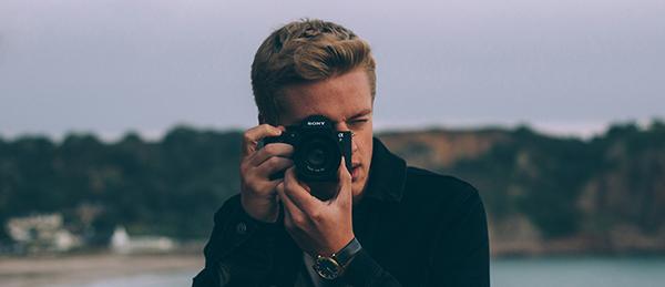 Kuvassa on kuvaaja kamera kädessä.